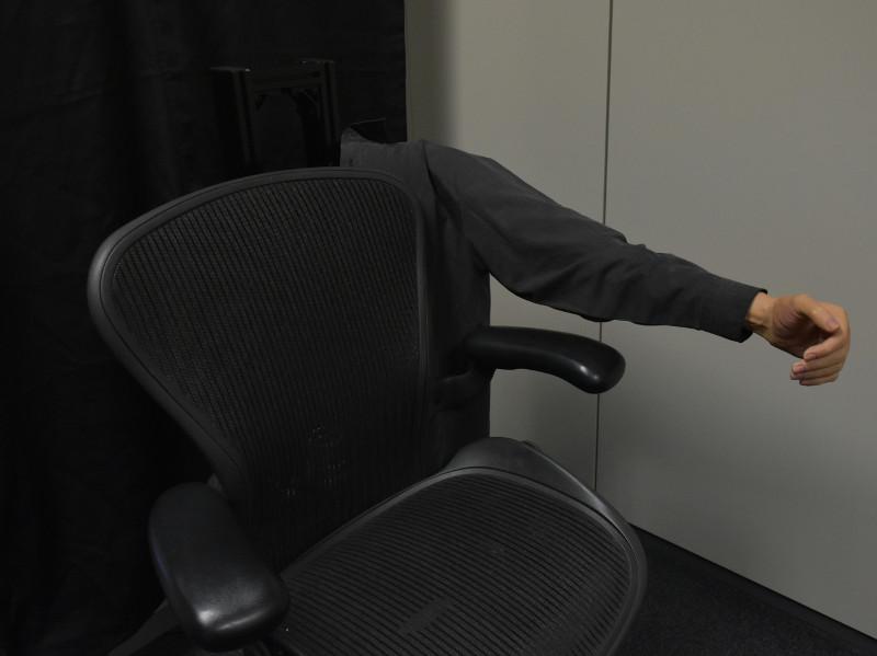 Gedankensteuerung von Roboterarm, neben einem Bürostuhl.