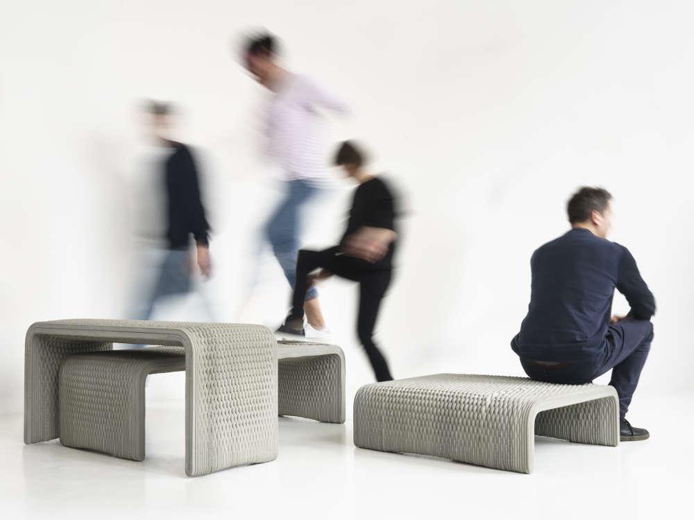 Mann sitzt auf Designer-Möbel aus Beton. Diese 3D-Bänke wurden mit den 3D-Betondrucker gedruckt.