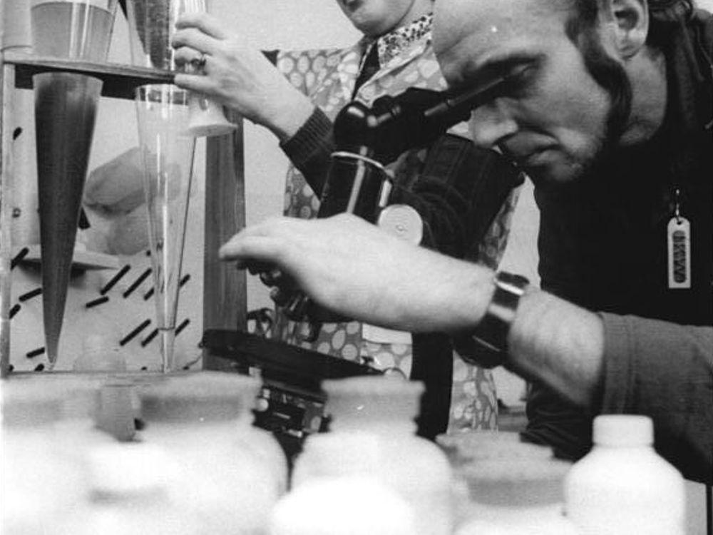 Man mit Mikroskop untersucht Proben.