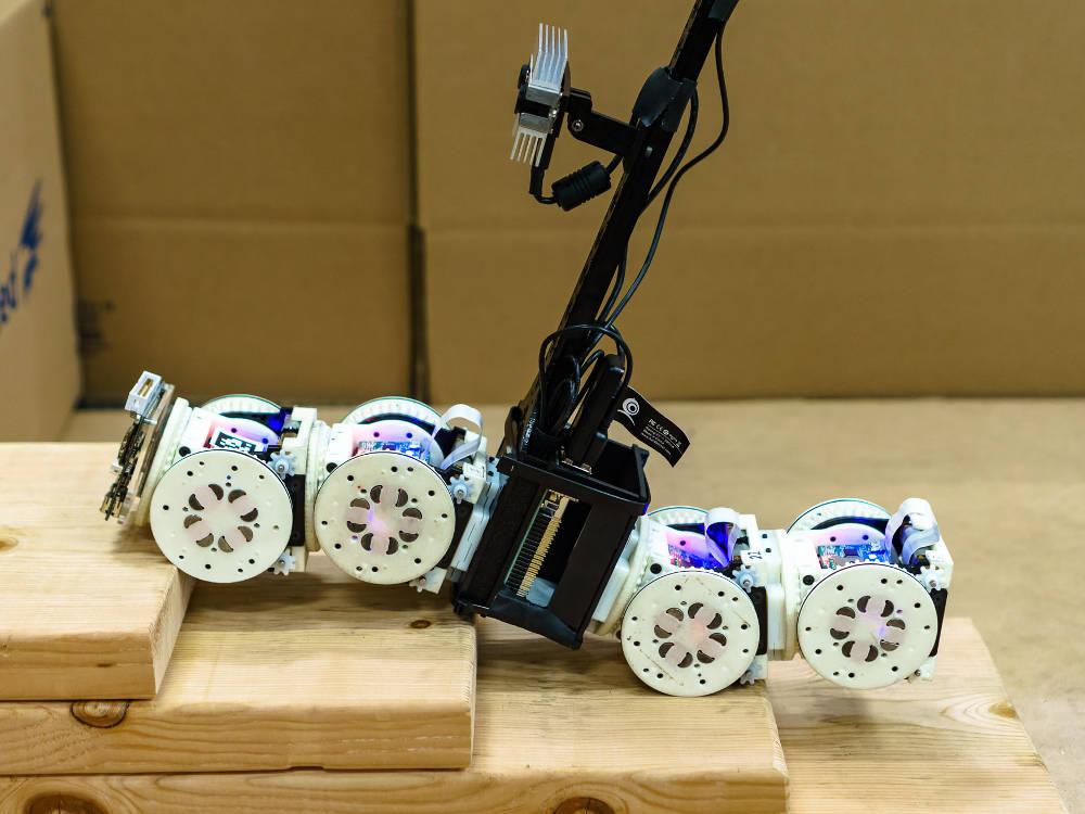 Ein Roboter mit SMORES Modulen überwindet ein Hindernis.