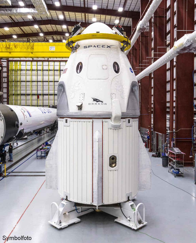 Crew-Dragon-Raumschiff von SpaceX neben einer Falcon 9 Rakete.