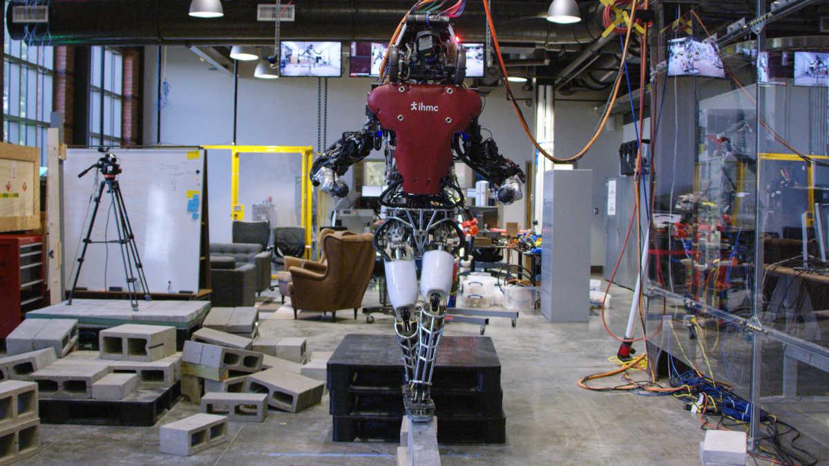 Ein Atlas-Roboter der Firma Boston Dynamics balanciert über einen Balken.