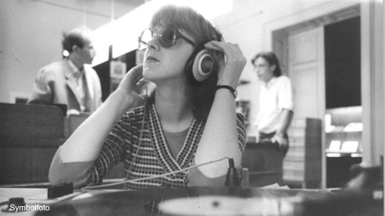 Eine junge Frau hört Musik von einer Schallplatte über einen Kopfhörer.