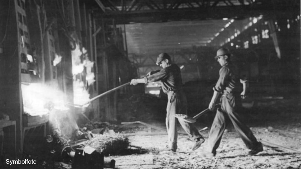 Schmelzer vor einem Stahlofen in einem Stahlwerk.