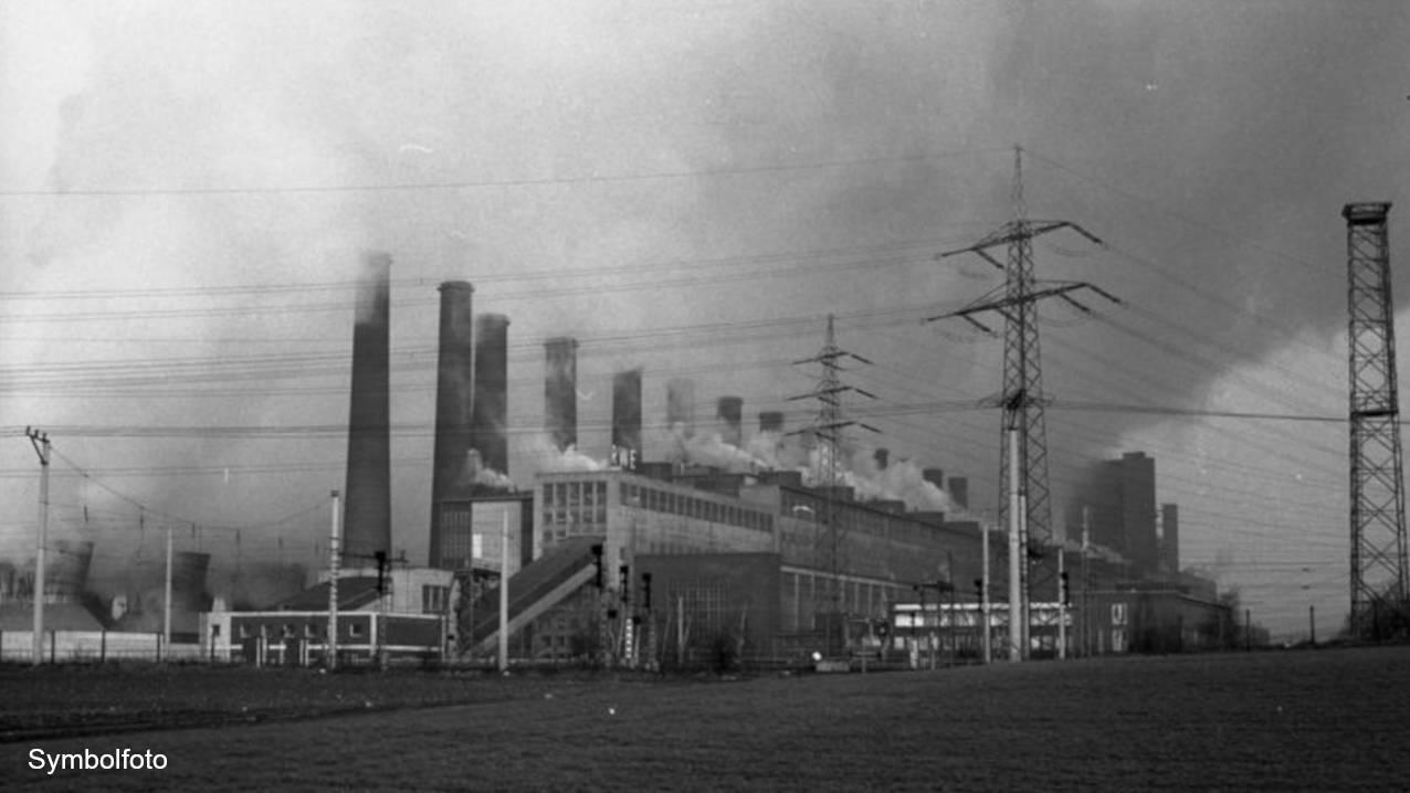 Rauchende Schornsteine eines Braunkohlekraftwerkes mit Strommasten.