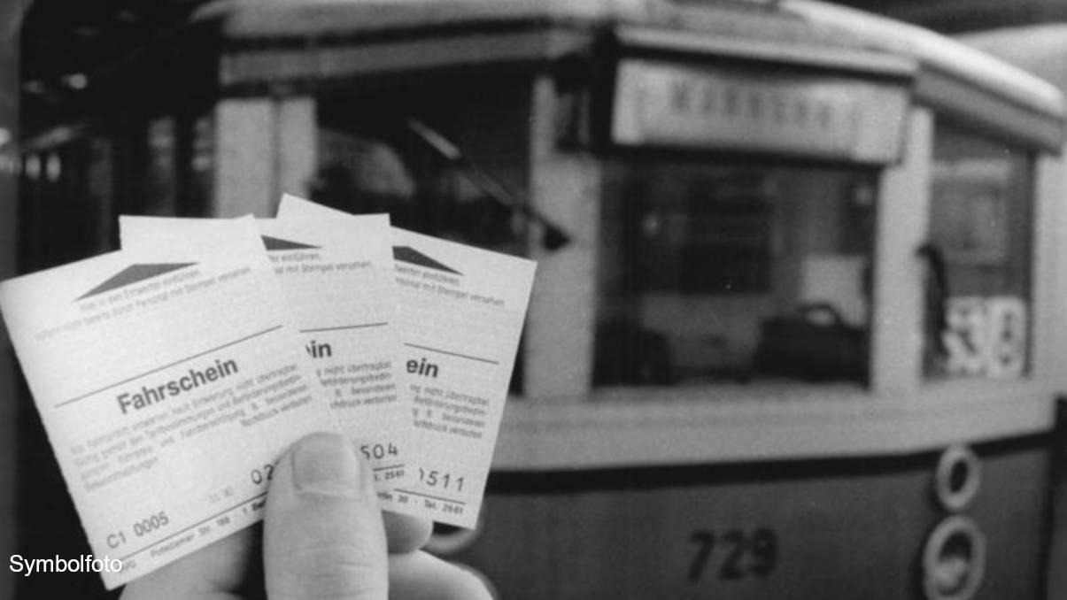 Jemand hält drei BVG-Fahrscheine vor einem S-Bahn-Zug im Hintergrund hoch.