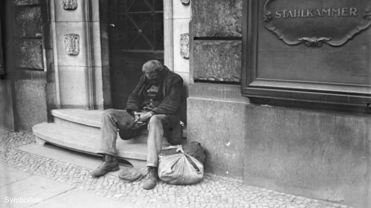 Ein Obdachloser sitzt auf einer Treppe und schläft.
