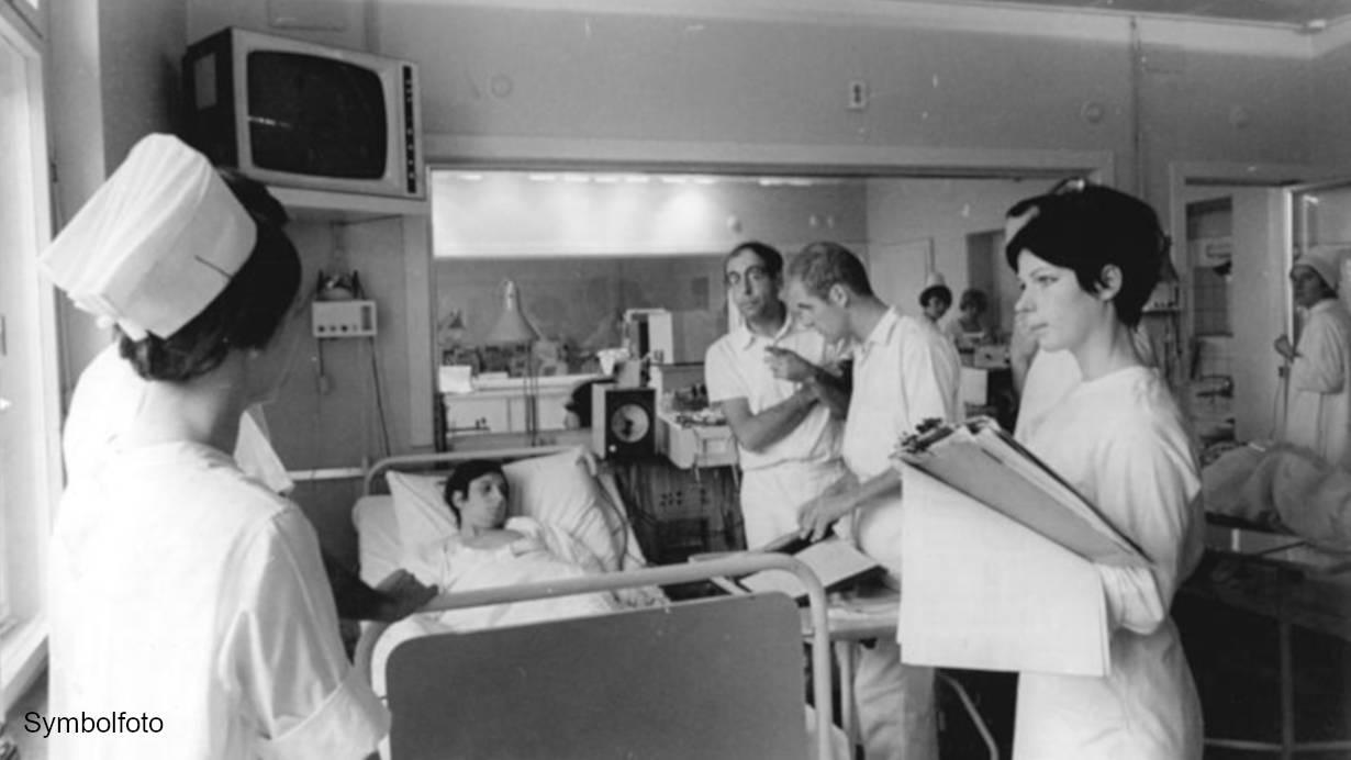 Ärzte legen während einer Visite beim Patienten die Therapie fest.