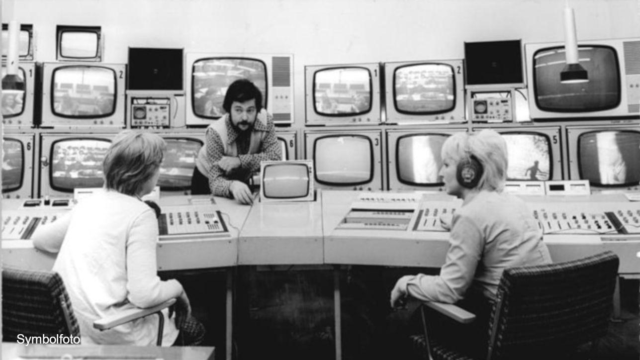 Regieraum mit drei Personen und vielen Bildschirmen