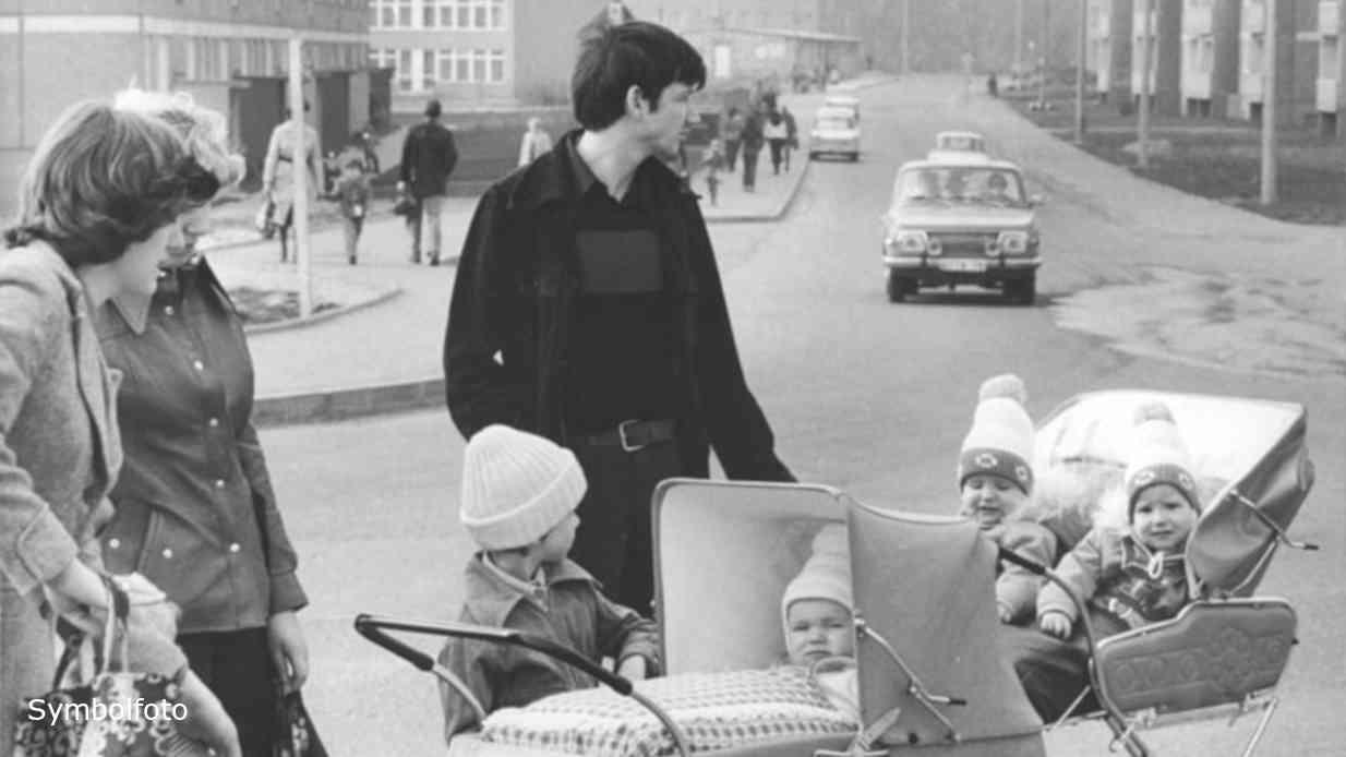 Eltern mit Kindern im Kinderwagen auf einer Straße.