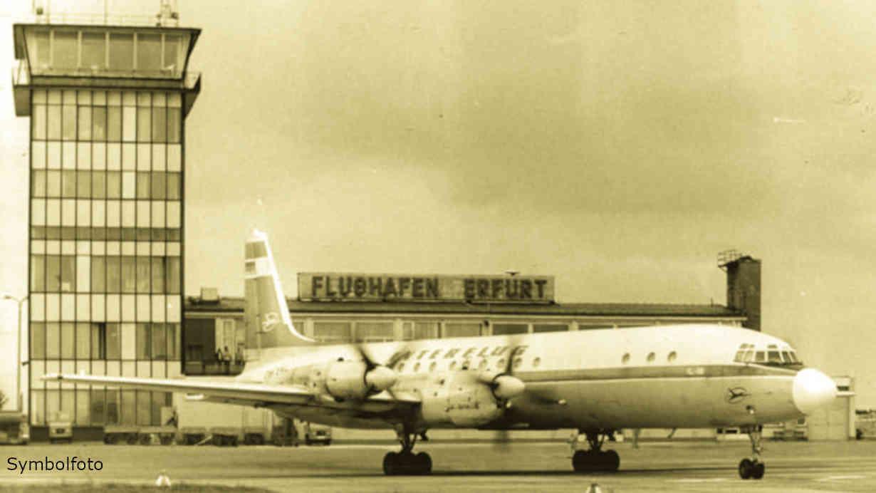 Flugzeug auf dem Weg zur Start- und Landebahn auf einem Flughafen vor dem Tower und Abfertigungsgebäude.