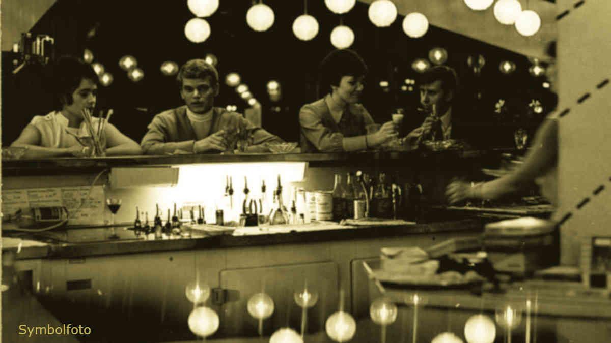 Gäste trinken an der Theke in einer Bar.