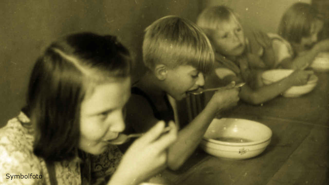 Mehrere Kinder essen gemeinsam an einem Tisch.