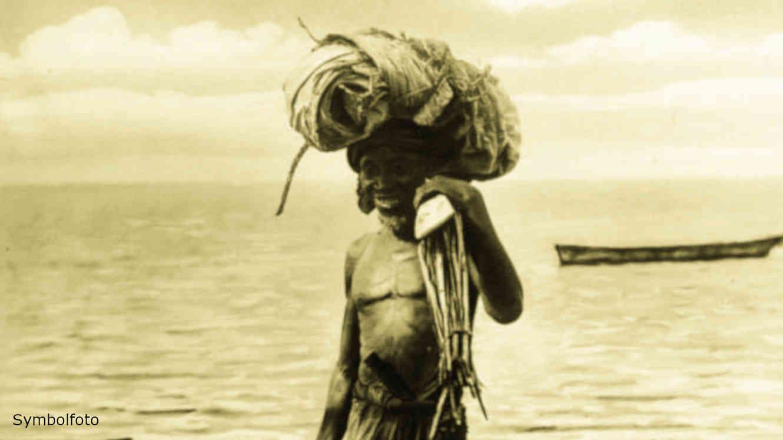 Ein Fischer am Strand in Afrika kommt vom Fischen. Im Hintergrund sieht man ein Fischerboot.