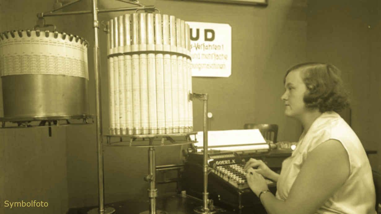 Eine Mitarbeiterin sitzt vor einer Rechenmaschine.