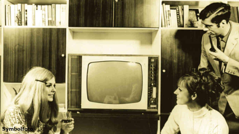 Frauen und ein Mann sitzen vor dem Fernseher.