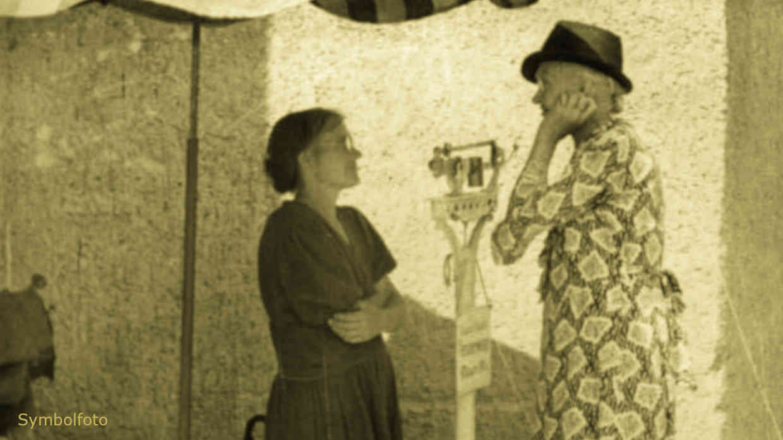 Zwei Frauen stehen sich gegenüber. Eine Frau wiegt ihr Gewicht auf einer Personenwaage, die auf der Straße steht.