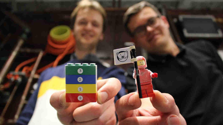 Wissenschaftler zeigen tiefgefrorene Lego-Figur und Legosteine.