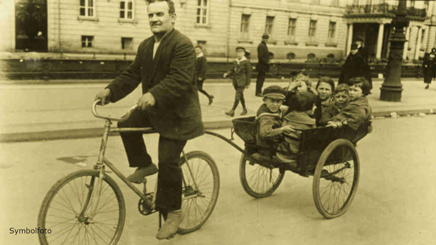 Hier sitzen sechs Kinder in einem Fahrrad-Anhänger.