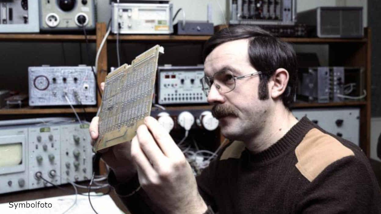 Ein Ingenieur betrachtet ein Elektronikbauteil.