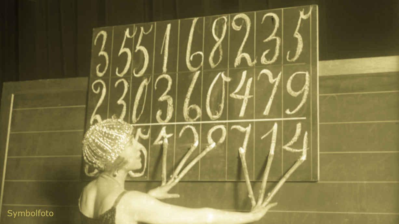 Eine Frau schreibt sechs verschiedene Zahlen mit sechs Fingern gleichzeitig auf eine Tafel.