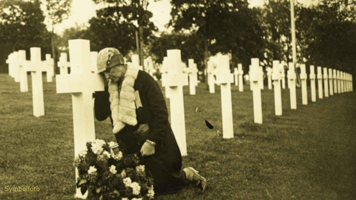 Ein Friedhof mit vielen Gräbern, auf dem eine Frau an einem Kreuz trauert.