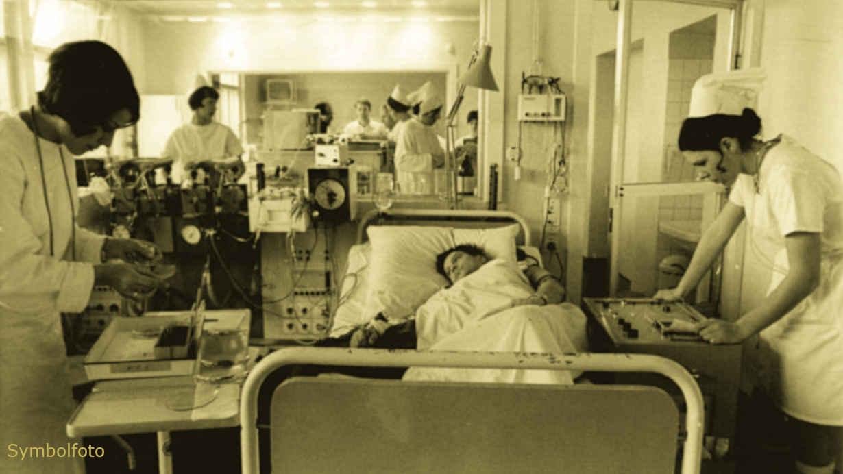 Ein Patient liegt in einem Bett im Krankenhaus, und um ihn herum sind viele Personen vom medizinischen Personal zu sehen.