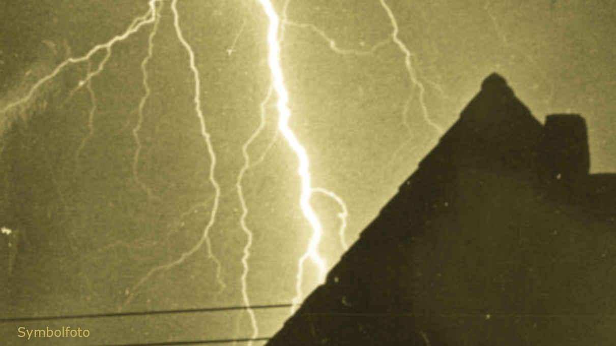Ein Blitz am Himmel, im Vordergrund steht ein Haus.