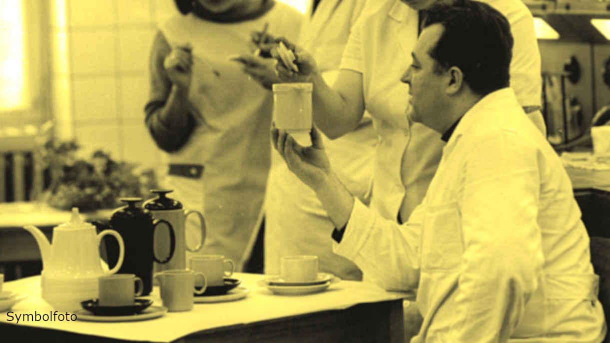 Ein Mitarbeiter hält ein Keramikkännchen in der Hand.